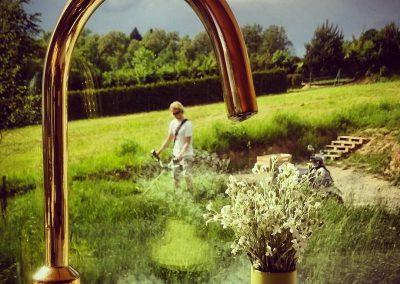 Złoty kran. Hary z kosiarą. Zlew. Mycie garów z widokiem na łąkę.